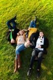 Quatre s'étendant sur l'herbe Images stock