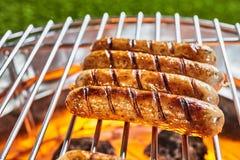 Quatre saucisses de proc juteuses grillant sur un BBQ image libre de droits