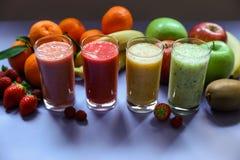 Quatre smoothies et baies différents d'ingrédients, banane, mandarine, kiwi, pomme Photographie stock