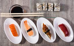 Quatre sortes Nigirisushi sur les soucoupes ovales et l'Uramaki Photographie stock