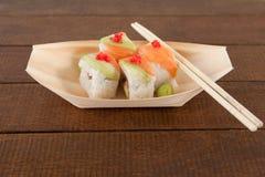 Quatre sushi d'uramaki ont servi avec des baguettes dans le plat en bois de bateau Image stock