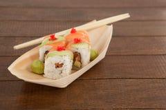 Quatre sushi d'uramaki ont servi avec des baguettes dans le plat en bois de bateau Photographie stock libre de droits