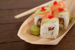 Quatre sushi d'uramaki ont servi avec des baguettes dans le plat en bois de bateau Photos stock