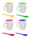 Quatre tasses colorées et quatre cuillères colorées Photo stock