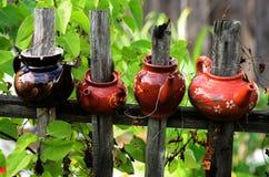 Quatre théières en céramique sur une barrière en bois Images libres de droits