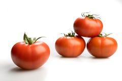 Quatre tomates rouges réalistes empilées vers le haut de d'isolement à l'arrière-plan blanc Image stock