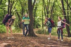Quatre touristes se sont arrêtés pour le repos dans la forêt, tenant la carte, tryin Images libres de droits