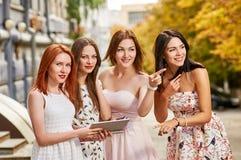 Quatre toursits d'amies regardant avec le PC de comprimé Photo stock
