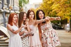 Quatre toursits de filles avec le PC de comprimé Pointage Photo libre de droits