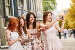 Quatre toursits de filles examinant le PC et le tir de comprimé Images libres de droits