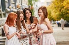 Quatre toursits de filles regardant dans le PC de comprimé Photographie stock libre de droits