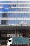 Quatre travailleurs lavant des fenêtres dans l'immeuble de bureaux Images libres de droits