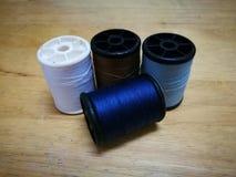 Quatre tubes de fil sont empilés au dos du bois Photos stock