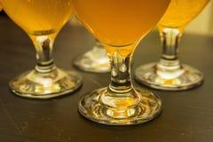 Quatre verres avec de la bière blonde Photographie stock libre de droits