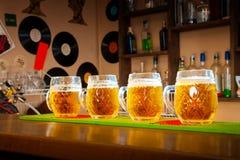 Quatre verres de bière se tiennent dans une rangée sur la table de barre Photographie stock libre de droits
