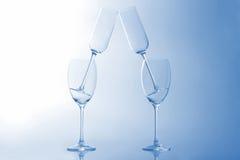 Quatre verres de vin vides sur un fond bleu-clair Photos stock