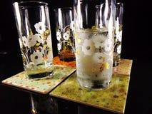 Quatre verres sur des caboteurs de boissons Photo libre de droits