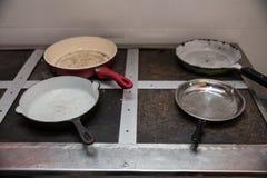 Quatre vieilles poêles d'un vieux plat industriel image stock