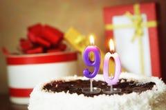Quatre-vingt-dix ans d'anniversaire Gâteau avec les bougies et les cadeaux brûlants Photo libre de droits