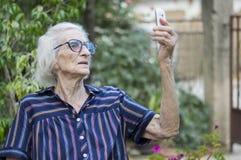 Quatre-vingt-dix grand-mamans d'années prenant un selfie avec un smartphone en Th Photos stock