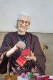 Quatre-vingt-dix grand-mamans d'années recevant son cadeau de Noël Photo stock