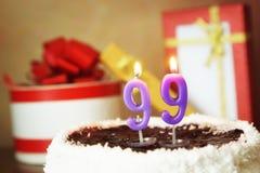 Quatre-vingt-dix-neuf ans d'anniversaire Gâteau avec la bougie et les cadeaux brûlants Photographie stock libre de droits