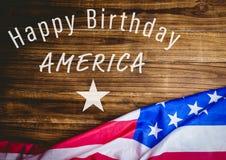 Quatrième de blanc de graphique de juillet contre la table en bois et le drapeau américain Photo libre de droits