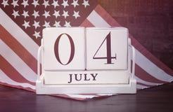 Quatrième du calendrier en bois de vintage de juillet avec le fond de drapeau Image stock