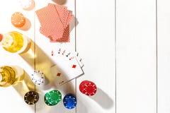 Quatro áss cercados por microplaquetas e por cerveja de pôquer no espaço de madeira branco do fundo e da cópia Fotos de Stock Royalty Free