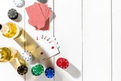 Quatro áss cercados por microplaquetas e por cerveja de pôquer no espaço de madeira branco do fundo e da cópia Foto de Stock Royalty Free
