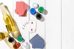 Quatro áss cercados por microplaquetas e por cerveja de pôquer no espaço de madeira branco do fundo e da cópia Imagem de Stock Royalty Free
