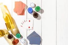 Quatro áss cercados por microplaquetas e por cerveja de pôquer no espaço de madeira branco do fundo e da cópia Imagem de Stock