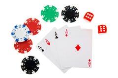 Quatro áss com as microplaquetas de pôquer diferentes e dados isolados no branco Fotos de Stock