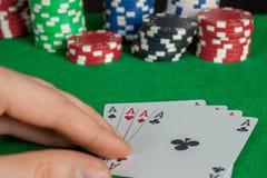 Quatro áss e pilhas das microplaquetas de pôquer na tabela verde Imagem de Stock