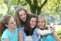 Quatro adolescentes atrativos em um parque fotos de stock