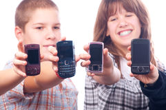 Quatro adolescentes felizes que mostram seus telemóveis Foto de Stock Royalty Free