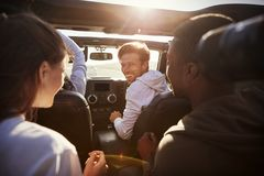 Quatro amigos adultos novos junto em um carro em uma viagem por estrada fotografia de stock royalty free