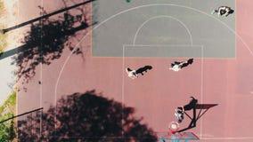 Quatro amigos aptos que jogam o basquetebol no à terra de esportes no ar livre vídeos de arquivo