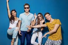 Quatro amigos bonitos estão rindo ao estar na frente da parede azul Entretenimento, tendo o bom tempo foto de stock