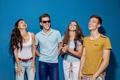 Quatro amigos bonitos estão rindo ao estar na frente da parede azul Entretenimento, tendo o bom tempo imagens de stock