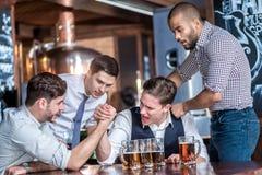 Quatro amigos competem às mãos da cerveja da bebida e passam o tempo t imagens de stock royalty free