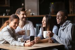 Quatro amigos diversos que têm o dispositivo do uso do divertimento que senta-se no café imagem de stock