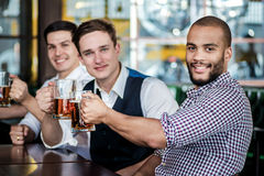 Quatro amigos dos homens de negócios bebem a cerveja e passam o tempo junto na fotografia de stock royalty free