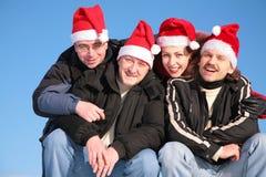 Quatro amigos em chapéus de Papai Noel foto de stock