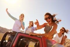 Quatro amigos fêmeas na viagem por estrada que está no carro convertível foto de stock