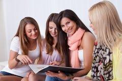 Quatro amigos fêmeas que olham um dobrador Foto de Stock Royalty Free