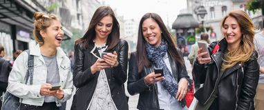 Quatro amigos felizes que andam na rua e que usam telefones celulares fotografia de stock royalty free