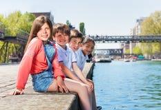 Quatro amigos felizes que sentam-se em uma linha na terraplenagem Imagens de Stock