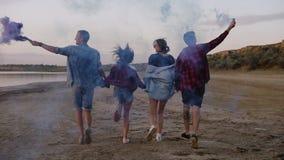 Quatro amigos na roupa ocasional que tem o divertimento junto Correndo e mantendo as mãos unidas Realizar dos meninos em suas mão filme