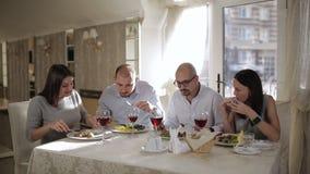 Quatro amigos no restaurante, comem a carne e para beber o vinho tinto no vidro filme